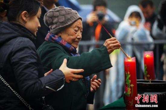 12月10日,南京大屠杀幸存者夏淑琴老人在侵华日军南京大屠杀遇难同胞纪念馆内祭拜遇难亲人。中新社记者 泱波 摄