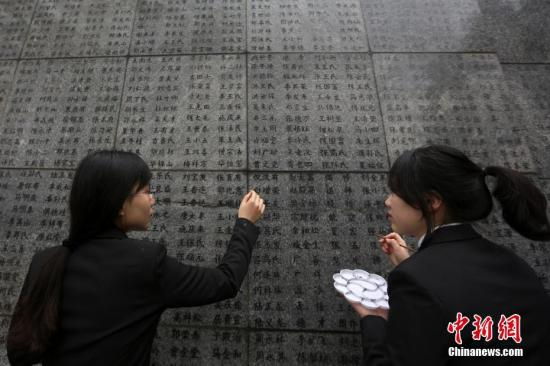 """12月10日,南京大学生志愿者为南京大屠杀遇难者名单墙(哭墙)上的遇难者名字""""描红""""。中新社记者 泱波 摄"""