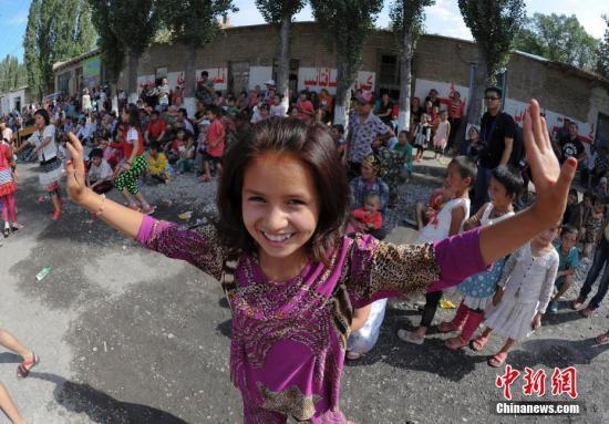 原料图:新疆农牧民们在街头跳首亲炎的麦西来甫舞蹈。中新社记者 刘新 摄