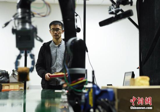 12月11日,柔性机器人手爪正在抓取蛋糕。中新社记者 韩苏原 摄