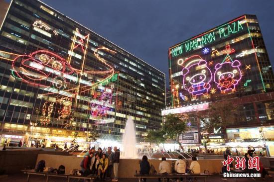 """临近圣诞节,香港荣华市区弥漫浓浓节日气氛,吸引大批旅客来港感受。近日,香港尖东海滨一带的商厦点亮了鲜艳的圣诞节灯饰,照耀维港两岸。即使圣诞节并非腹地伪期,但受惠""""一桥一铁""""通车带动,香港零售市道向益。据香港旅游发展局数据表现,今年始九个月,访港旅客达4668.1万人次,按年添9.5%。当中,腹地旅客约3249.9万人次,升12.7%。图为12月10日华灯初上的香港尖沙咀东部。中新社记者 洪少葵 摄"""