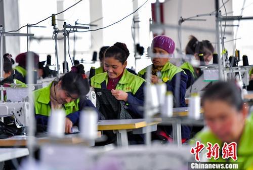 12月初,新疆喀什一家服装公司服装添工车间里,员工正在赶驯服装订单。中新社记者 刘新 摄