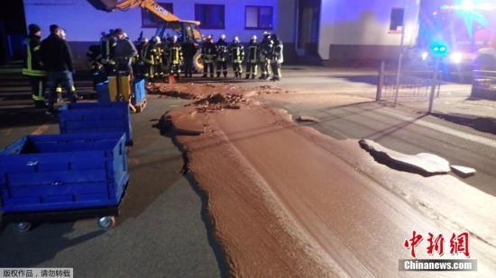 当地时间12月10日,一辆运输液体巧克力的汽车在德国韦尔(Werl)附近发生泄漏,导致公路被巧克力所覆盖。图为当地消防人员正在清理凝固的巧克力。