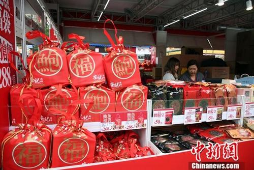 12月14日,一家参展商在工展会上,准备大批优惠的福袋。中新社记者 洪少葵 摄