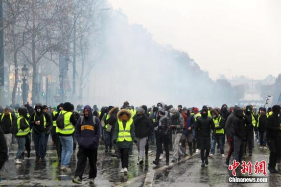 原料图:警方在巴黎香榭丽弃大街向示威者施放催泪瓦斯,试图将示威者驱散。中新社记者 李洋 摄