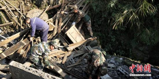 武警官兵深入震区帮助群众清理废墟中的可用物资。姜永安 李华时 刘崇达摄影报道