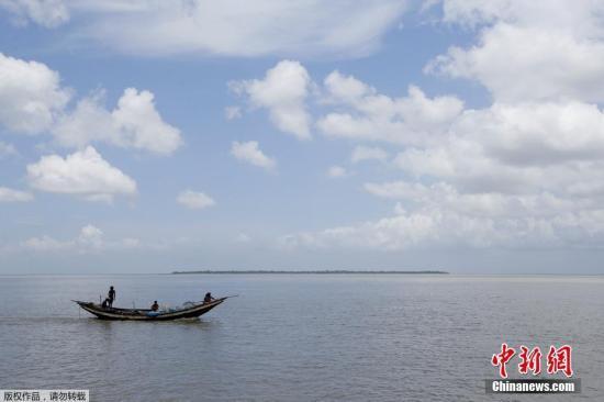 资料图:受全球海平面上升影响,葛拉马拉岛将被海水淹没。图为一名渔民和他的家人乘船经过葛拉马拉岛。