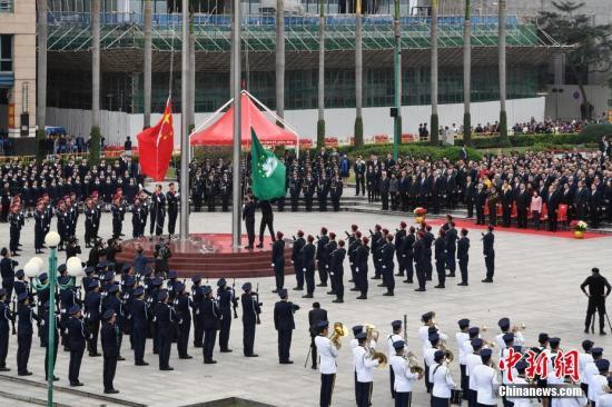 12月20日上午8时,澳门特区当局在澳门金莲花广场举走升旗仪式,祝贺澳门回归故国19周年。图为升旗仪式。中新社发 钟欣 摄