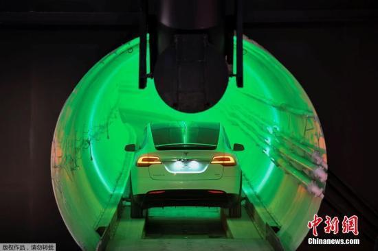"""当地时间12月18日,美国科技企业家马斯克在加州霍桑市展示了其""""钻孔公司""""(Boring Company)打造的第一条地下隧道。据外媒报道,马斯克乘坐一辆改装过的特斯拉汽车,从这条长1.8公里、直径3.7米的隧道一端现身。"""