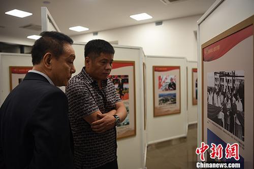 巴西华人协会会长张伟(右)等侨领参不益看图片展。中新社记者 莫成雄 摄
