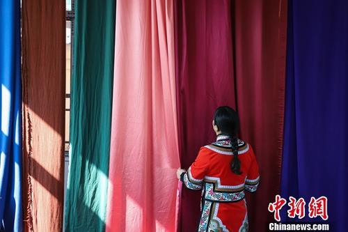 """12月21日,当地村民罗晓梅在选取布料。当日,在贵州省毕节市赫章县珠市乡的一家民族服装生产企业,来自当地的多位妇女正在服装加工设备前忙碌工作。据悉,该企业主要生产销售彝族服饰、彝族刺绣工艺品、旅游小商品等产品,采取""""公司+农户""""的生产模式,带动传统手工艺人在家就业,解决了周边77户100名贫困妇女的就业问题。<a target='_blank' href='http://www.chinanews.com/'>中新社</a>记者 瞿宏伦 摄"""
