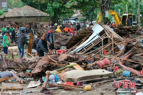图为印度尼西亚卡里塔的灾民在受海啸损坏的房屋内检查被困者。