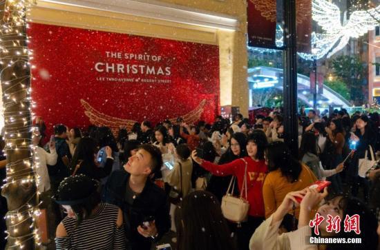 """资料图:2018年12月22日晚,香港湾仔利东街热闹非凡,一场如约而至的""""大雪""""吸引众多游客拍照留念。中新社记者 张炜 摄"""
