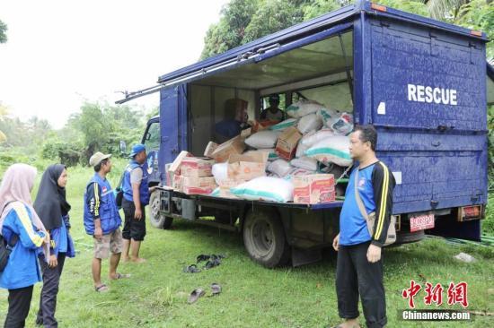 当地时间22日晚,印尼巽他海峡发生海啸,造成万丹省海边居民和游客重大人员伤亡,数百栋房屋被毁。图为当地救灾部门在分发救灾物资。中新社记者 林永传 摄