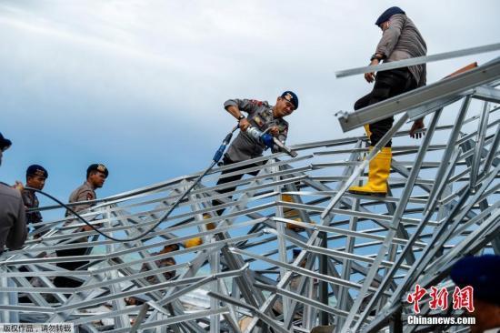 当地时间12月24日,印尼巽他海峡海啸声援做事睁开,印尼当局、军队、红十字会以及自愿者所构成的声援队伍正在灾区开展搜救做事。图为警方在一间滨海酒店的废墟上搜寻遇难者。