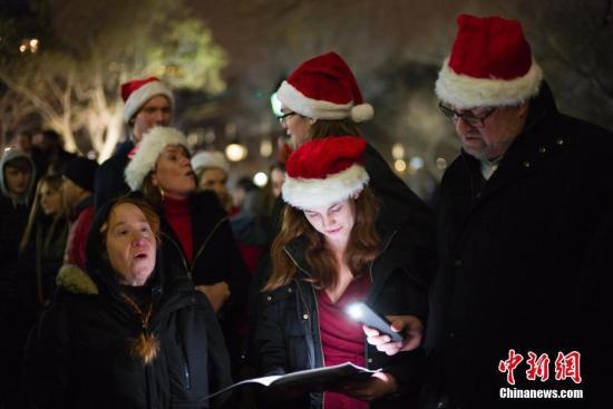资料图:民众在平安夜聚集纽约华盛顿广场共唱圣诞颂歌。中新社记者 廖攀 摄