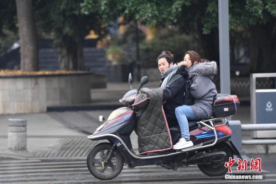 资料图:市民骑行在寒风中。 张浪 摄