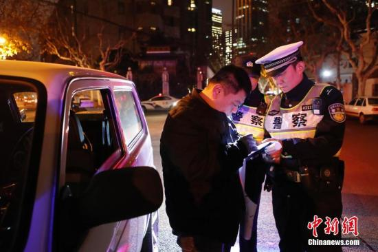 2018年12月24日至25日凌晨,徐汇公安分局交警对违法司机进行当场处置。中新社记者 殷立勤 摄
