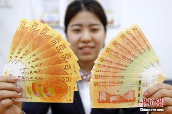 资料图:中国人民银行发行的人民币发行70周年纪念钞与改革开放40周年纪念币。张云 摄