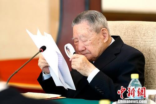 """资料图:12月28日,""""改革开放40周年国际法工作座谈会""""在北京举行。图为荣获改革先锋称号的外交部原法律顾问、联合国国际法院原院长史久镛用放大镜查阅文件。<a target='_blank' href='http://www-chinanews-com.3amt.com/'>中新社</a>记者 富田 摄"""