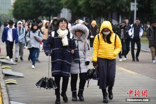 资料图:寒风中的行人。王以照 摄