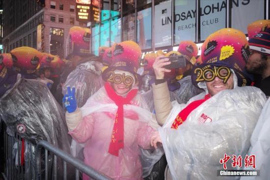 当地时间12月31日,纽约时报广场举行一年一度的跨年庆典,尽管当日一直降雨,仍吸引了成千上万的人们在寒雨中迎接新年。图为雨中参加庆典的人们。<a target='_blank' href='http://www.chinanews.com/'>中新社</a>记者 廖攀 摄