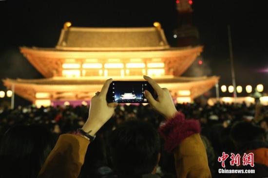 """资料图:日本人把12月31日称为""""大晦日""""(相当于中国的除夕)。许多日本民众当晚会来到附近的神社或寺庙聆听新年钟声敲响,并进行新年的首次参拜(日本称为""""初诣"""")。图为日本民众在东京增上寺跨年的场景。<a target='_blank' href='http://www.chinanews.com/'>中新社</a>记者 吕少威 摄"""