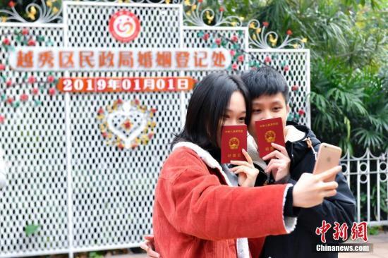 """1月1日,一对新人领取结婚证后在日期板前合影留念。2019年1月1日是新年首天,""""一生一世一双人""""的寓意吸引不少新人在当天办理结婚登记。据广州市民政局统计,截至当天12时,广州办理结婚登记451对。中新社记者 陈骥旻 摄"""