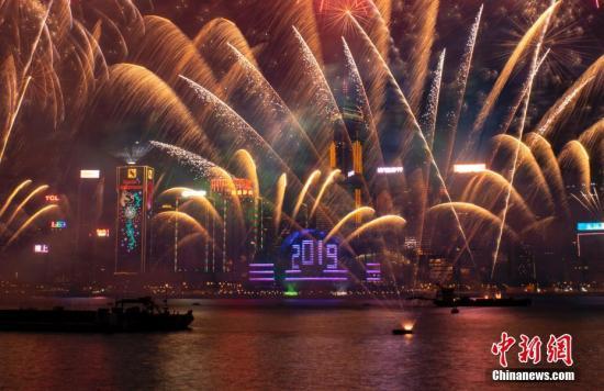 """2019年1月1日0时,历时10分钟的""""烟火音笑汇演在香港维多利亚港上空正式上演。陪同着涟漪的音笑,鲜艳烟花在空中绽放,幻彩光束在空中闪烁,会展中间玻璃幕墙上展现巨型""""2019""""字样。数十万香港市民和游客在九龙、港岛等地不雅旁观这场声、光、烟花交织在一首的跨年盛会,共同接待新年到来。中新社记者 张炜 摄"""