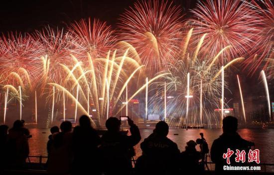 """2019年1月1日0时,当新年钟声响首,历时10分钟的""""烟火音乐汇演在香港维众利亚港上空正式上演。陪同着泛动的音乐,鲜艳烟花在空中绽放,幻彩光束在空中闪烁,会展中心玻璃幕墙上展现巨型""""2019""""字样。数十万香港市民和游客在九龙、港岛等地不雅旁观这场声、光、烟花交织在一首的跨年盛会,共同欢迎新年到来。中新社记者 张炜 摄"""