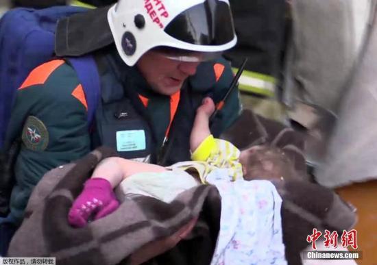 当地时间1月1日,俄罗斯马格尼托尔斯克市一座住宅楼发生瓦斯爆炸事件后,救援人员怀抱被救出废墟的11个月大男婴。日前,该住宅楼发生天然气爆炸,部分大楼坍塌,导致多人死伤,目前仍有人失踪。(视频截图)