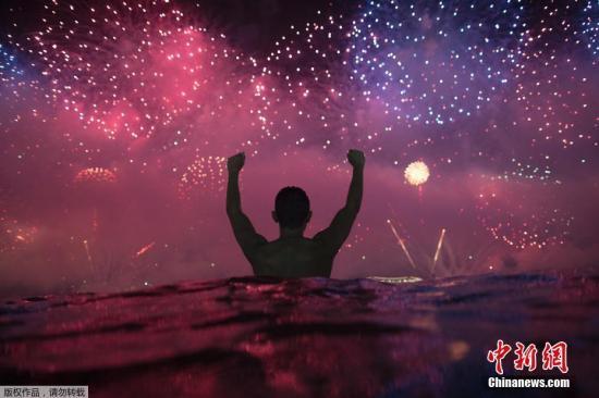 資料圖:當地時間2019年1月1日凌晨,民眾在水中觀看巴西里約熱內盧科帕卡巴納海灘新年煙火表演。