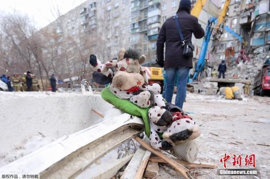2018年12月31日,俄车里雅宾斯克州马格尼托哥尔斯克市一居民楼天然气爆炸。事发后俄各方紧急组织救援,但废墟再次坍塌的风险以及夜间严寒使得救援难度加大。图为事故现场摆放的满是尘土的玩偶。