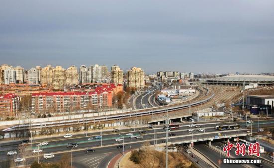 """1月5日,17辆超长版时速350公里复兴号动车组首次亮相京沪高铁。据了解,此次首次投入运营的17辆超长版""""复兴号""""动车组全长439.9米,载客定员1283人,载客能力较16辆编组提升了7.5%,担当北京南至上海虹桥G9/G16次列车运行任务。图为17辆超长版时速350公里""""复兴号""""动车组G9次列车驶离北京南站。<a target='_blank' href='http://fyand.com/'>中新社</a>记者 卞正锋 摄"""