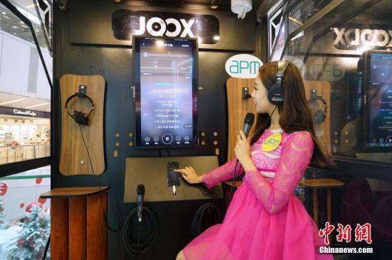 """1月7日,以潮流电玩影音为主题的""""潮流科技无人店""""在香港观塘apm商场开业,该无人店面积约1000平方�眨�设有潮流电玩影音、贺年潮货、自助卡拉OK等主题区,顾客在无人店内选购商品后只需站在出口处的""""感应结算区域"""",系统会自动识别商品,然后用微信支付扫描二维码即可付款,实现全程自助购物和结算。图为模特在无人店自助卡拉OK站自助选歌试唱。<a target='_blank' href='http://bharatcinema.com/'>中新社</a>记者 张炜 摄"""