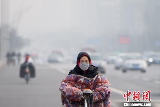 1月7日,山西省太原市被重度霾笼罩,民众戴口罩出行。 韦亮 摄
