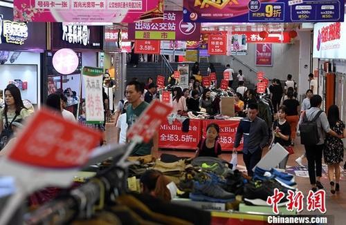 图为厦门市民在一商场内选购打折商品。(资料图片)中新社记者 张斌 摄