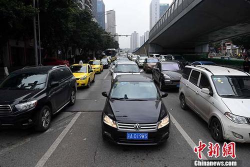 资料图:重庆市渝北区,车辆排队通过红绿灯。 中新社记者 陈超 摄
