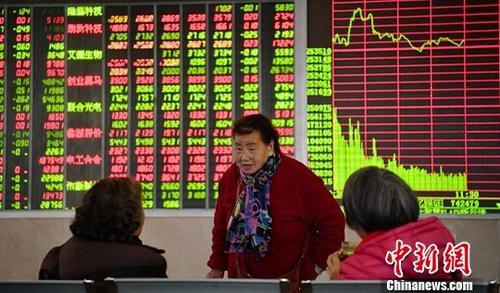 资料图 1月11日,股民在四川成都某证券交易大厅内讨论交流。中新社记者 刘忠俊 摄