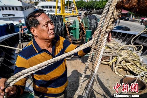 1月11日,海南省琼海市潭门海上民兵连副连长王书茂正在船上整理缆绳。中新社记者 骆云飞 摄