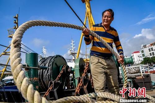 """1月11日,海南省琼海市潭门海上民兵连副连长王书茂正在船上整理缆绳。在2018年12月18日召开的庆祝改革开放40周年大会上,王书茂被授予""""改革先锋""""称号,他是海南省唯一获此殊荣的个人。1985年,当29岁的海南潭门渔民王书茂第一次以""""海上民兵""""的身份驶向浩瀚南海,他立志做好一件事:守护""""祖宗海""""。中新社记者 骆云飞 摄"""