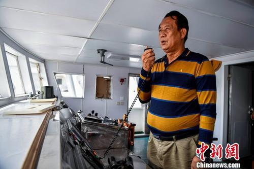 1月11日,海南省琼海市潭门海上民兵连副连长王书茂正在船上调试通讯设备。中新社记者 骆云飞 摄