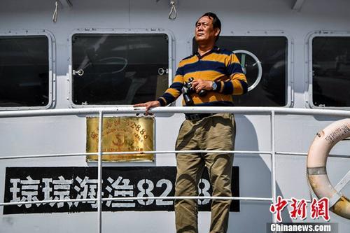 1月11日,海南省琼海市潭门海上民兵连副连长王书茂正在船上远望大海。中新社记者 骆云飞 摄