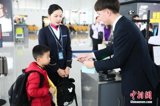 资料图:1月13日,广州白云机场,地面工作人员陪同无陪儿童前往登机口。刘艺 摄