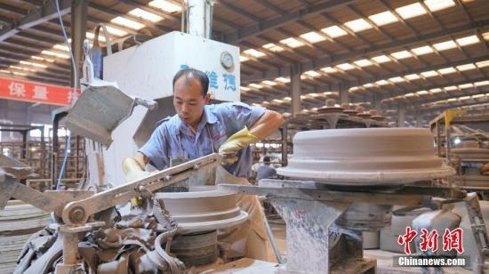 原料图:企业员工正在做作机器。 中新社记者 陈峰 摄