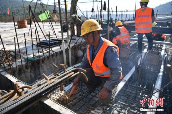 1月16日,由中铁隧道局集团承建的中(国)老(挝)国际大通道玉(溪)磨(憨)铁路立新寨四线特大桥顺当相符龙,标志着中老铁路又一重点工程取得突破。立新寨四线特大桥是玉磨铁路首座相符龙的四线特大桥,位于云南省元江县铜厂冲村,全长952.8米。图为施工人员进走作业。中新社记者 刘冉阳 摄