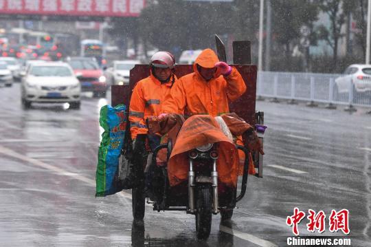 资料图:两位环卫工人在风雪中前行。杨华峰摄