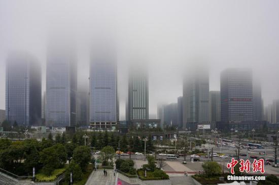 1月18日,贵阳市观山湖区出现浓雾,高楼大厦若隐若现。中新社记者 贺俊怡 摄