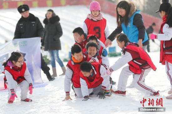 """1月18日,北京玉渊潭公园开展""""欢乐迎冬奥 寒假冰雪梦""""雪地趣味运动会,来自北京外国语大学附属小学的学生在雪地上充分展示着青春活力,雪地曲棍球、雪地青春竞速、雪地牵钩拔河、雪地足球等项目不但提升孩子们身体素质,也为推动冰雪运动发展拓展了空间。<a target='_blank' href='http://www.chinanews.com/'>中新社</a>记者 杜洋 摄"""