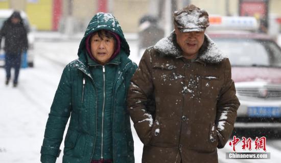 """1月20日,兰州迎来降雪天气。当日是二十四节气中最后一个节气""""大寒""""。图为市民雪中出行。记者 杨艳敏 摄"""